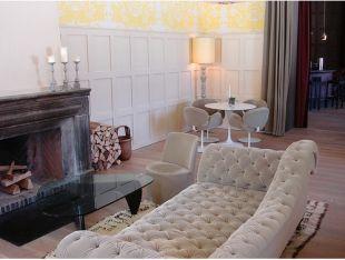 Gyönyörű gombbehúzásos kanapé a kandalló előtt